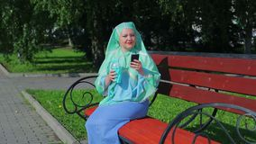 A young Muslim woman in a light scarf is shed on a bench in the park and drinks coffee and talks in the messenger. Overall plan stock footage