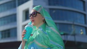 A young Muslim woman in a light scarf and sunglasses against the background of a modern building. The average plan stock video footage