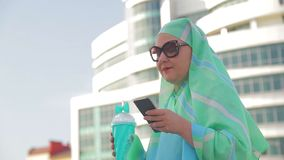 A young Muslim woman in a light scarf and sunglasses against the background of a modern building. The average plan stock video