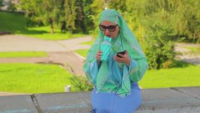 A young Muslim woman in a light scarf and sunglasses in the park drinks coffee and is in the messenger. The average plan stock footage