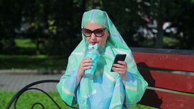 A young Muslim woman in a light scarf and sunglasses is sitting on a bench in the park and drinking coffee and talking. In the messenger. The average plan stock video footage