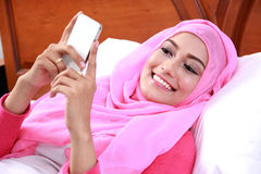 Young muslim woman lying on bed while playing mobilephone. Portrait of cheerful young muslim woman lying on bed while playing mobilephone Royalty Free Stock Photos