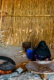 Young muslim woman with masked face cooking bread in a bedouin dwelling stock photos