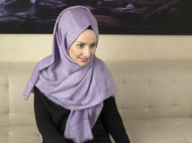 Young muslim woman in office on sofa. Young muslim woman portrait with islamic dress and scarf Stock Photos