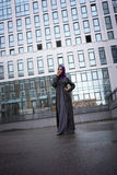 Young Muslim woman in oriental dress on a background of a modern building. With a glass facade Stock Image