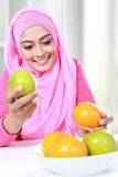 Young muslim woman pick over between apple and orange Stock Images