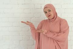 Young muslim woman in pink hijab clothes isolated on white background. People religious lifestyle concept stock photo