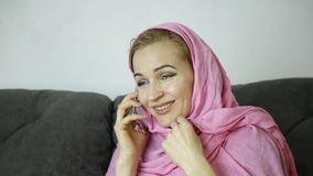 Young Muslim woman in pink hijab sitting on a sofa in a cafe and talking on cell phone stock video footage