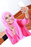 Young muslim woman posing taking selfie photo. Portrait of young muslim woman posing taking selfie photo with mobilephone on bed Royalty Free Stock Photography