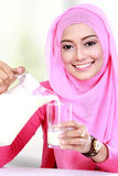 Young muslim woman pouring milk into a glass royalty free stock photography
