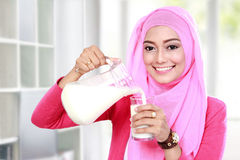 Young muslim woman pouring milk into a glass Stock Photography