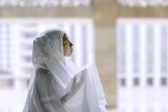 Young muslim woman praying in the mosque. While wearing islamic clothes Royalty Free Stock Photo