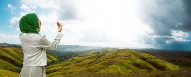 Young muslim woman praying. Standing on mountain Royalty Free Stock Photo