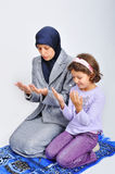 Young muslim woman praying on traditional way. Muslim young woman praying with her daughter to teach her Royalty Free Stock Images