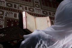 Young muslim woman reading Koran Stock Image