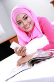Young muslim woman reading a magazine Royalty Free Stock Images