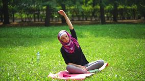 Young muslim woman in a scarf stretches her spine in the park on a summer day stock video footage