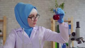 Young muslim woman scientific chemist laboratory assistant in the national scarf working in the laboratory slow mo stock video