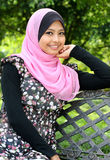 Young muslim woman is sitting on the bench. In autumn park and looking at camera Royalty Free Stock Images