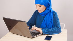 Young Muslim woman sitting in office and working on laptop stock footage