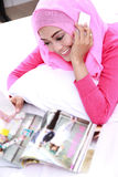 Young muslim woman talking on the phone while enjoy reading Stock Photos