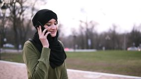 A young muslim woman in a traditional headscarf chatting with friends on a smartphone in the park, a lady walks along. The park in black hijab on a cloudy day stock video footage