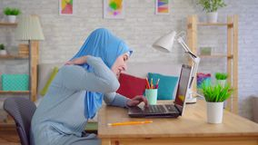 Young Muslim woman in a traditional headscarf slouches while sitting at a laptop and feels pain in her neck