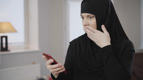 Young muslim woman in traditional hijab looking at smartphone screen and making shocked facial expression. Eastern