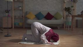 Muslim woman in a traditional scarf praying on rug in her living room. Young muslim woman in a traditional scarf praying on rug in her living room stock video