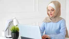 Young muslim woman is typing on laptop working in office. royalty free stock photography