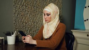 Young Muslim woman using smart phone in cafe. Young Muslim woman spending leisure time in cafe and typing message on mobile phone. Everyday life of modern Muslim stock video