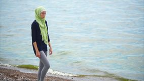 A young Muslim woman in a veil comes with a pensive look along the sea stock video