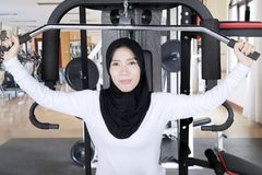 Young Muslim woman with weight machine. Young Muslim woman looking at the camera while doing a workout with weight machine in the fitness center Stock Images