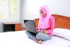 Young muslim woman work using laptop on bed Royalty Free Stock Images