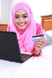 Young muslim woman work using laptop and holding a credit card Royalty Free Stock Photography