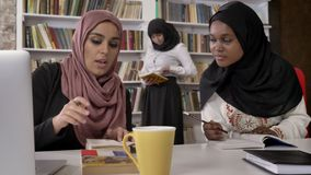 Young muslim women in hijab explaining something to black women in hijab, studying in library and preparing for exams.