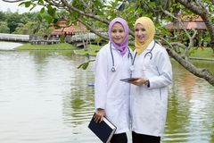 Young muslimah doctor standing and having discussion at park during lunch hour. Stock Image