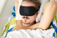 Young mustached husband sleeping with sleep mask Stock Image