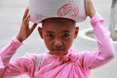 Young Myanmar nun carrying rice Stock Photos
