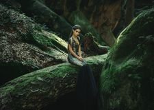 A young mysterious girl. A dark princess sits on a log among the rocks. Gothic photosession theme of Halloween. Unusual, creative outfit stock images