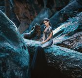 A young mysterious girl. A dark princess sits on a log among the rocks. Gothic photosession theme of Halloween. Unusual, creative outfit royalty free stock photos