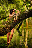 Young naked beautiful Caucasian woman standing in water in rainforest with eyes closed, hiding behind a tree. Royalty Free Stock Photos