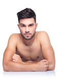 Young naked beauty man sitting at a table Royalty Free Stock Photography