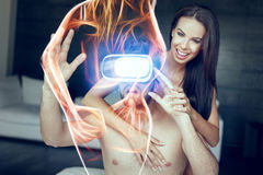 Young naked couple foreplay with virtual reality headset, playin. G with fiery virtual woman royalty free stock photos