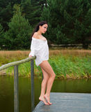 Young naked girl in white shirt  posing on the bridge Royalty Free Stock Image