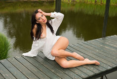 Young naked girl in white shirt  posing on the bridge Royalty Free Stock Images