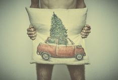A young naked man covers his with a pillow with a Christmas themed pattern. business after New year royalty free stock photography