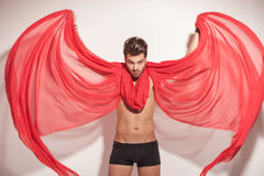 Young naked man fluttering a red textile Stock Photo