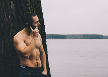 Young Naked Man. Young man with phone near the tree on lake Royalty Free Stock Images