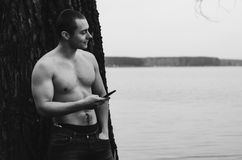 Young Naked Man. Young man with phone near the tree on lake. Black and white photo Stock Image